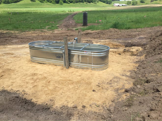 The newly installed watering facility for the lower pasture with a constant flow of spring water. Notice the gravel surrounding the tank. This assists in stabilizing the area and improving the cattle access during times of high moisture.