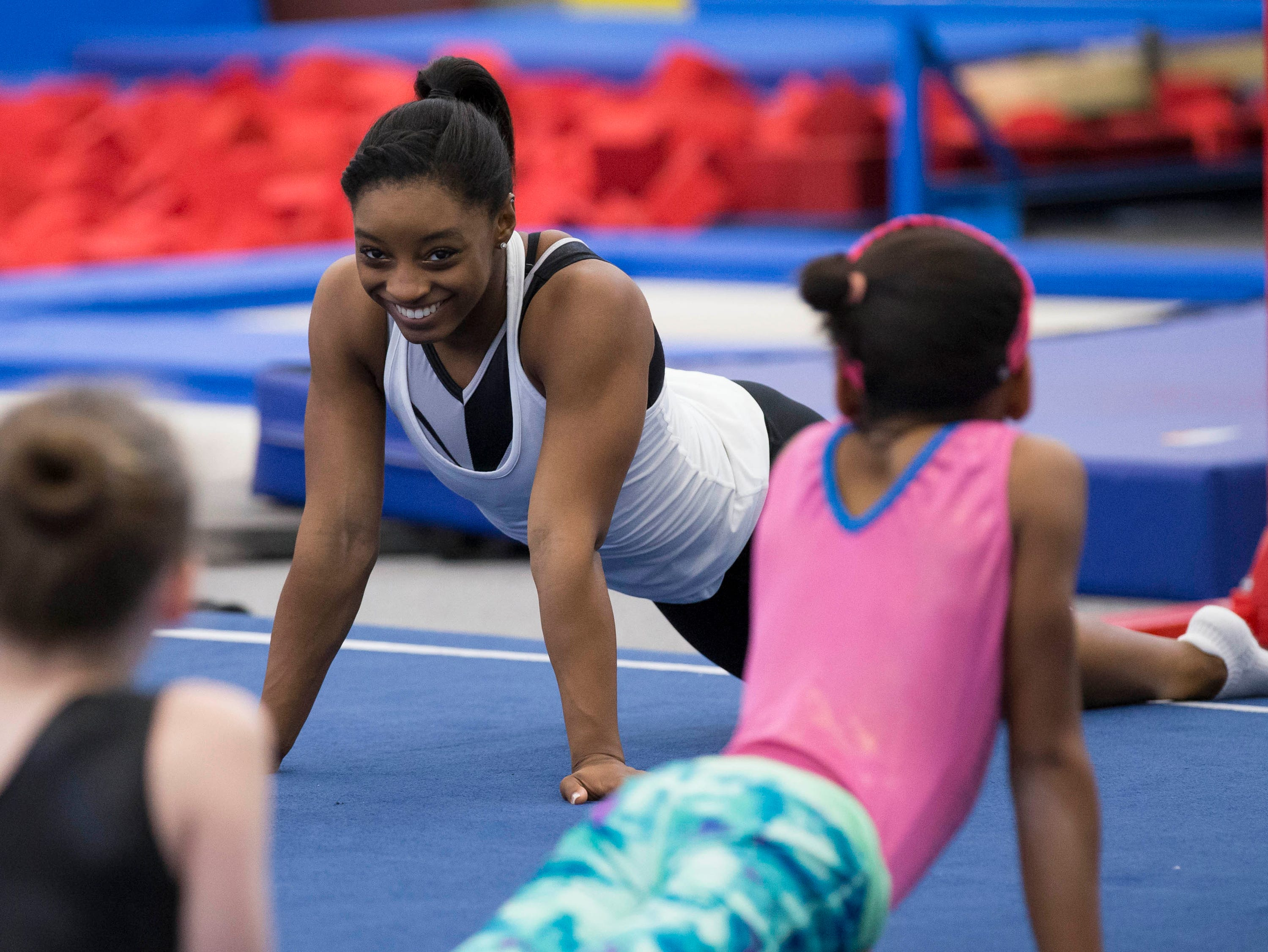 In 2015, Simone Biles chats with gymnasts during a training camp.
