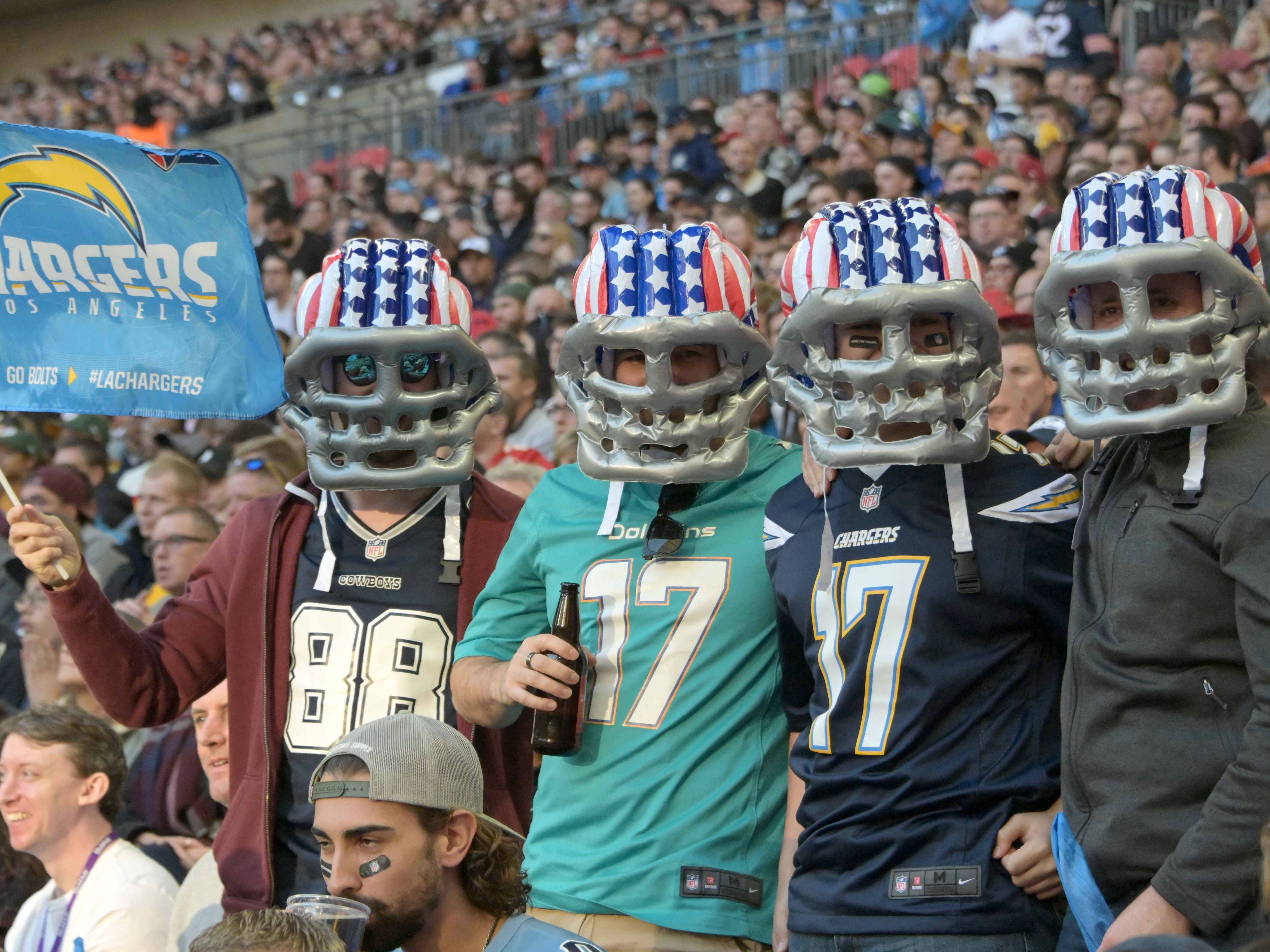 Fans pose with a Los Angeles Chargers flag during an NFL International Series game against the Tennessee Titans  at Wembley Stadium.