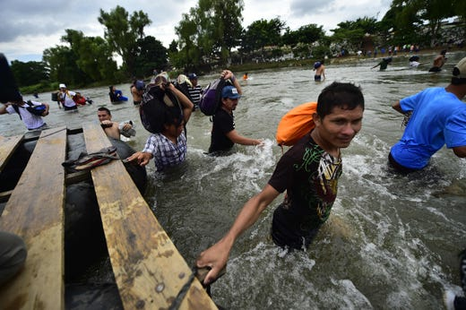 Honduran migrants heading in a caravan to the US, arrive in Ciudad Hidalgo, Chiapas state, Mexico after crossing the Suchiate River from Guatemala, on October 20, 2018. - Thousands of migrants who forced their way through Guatemala's northwestern border and flooded onto a bridge leading to Mexico, where riot police battled them back, on Saturday waited at the border in the hope of continuing their journey to the United States.