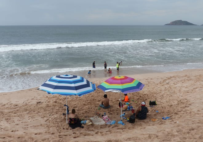 Tourists enjoy the beach in Mazatlan, in Mexico's Sinaloa state, where Hurricane Willa is expected to land Oct. 23, 2018.
