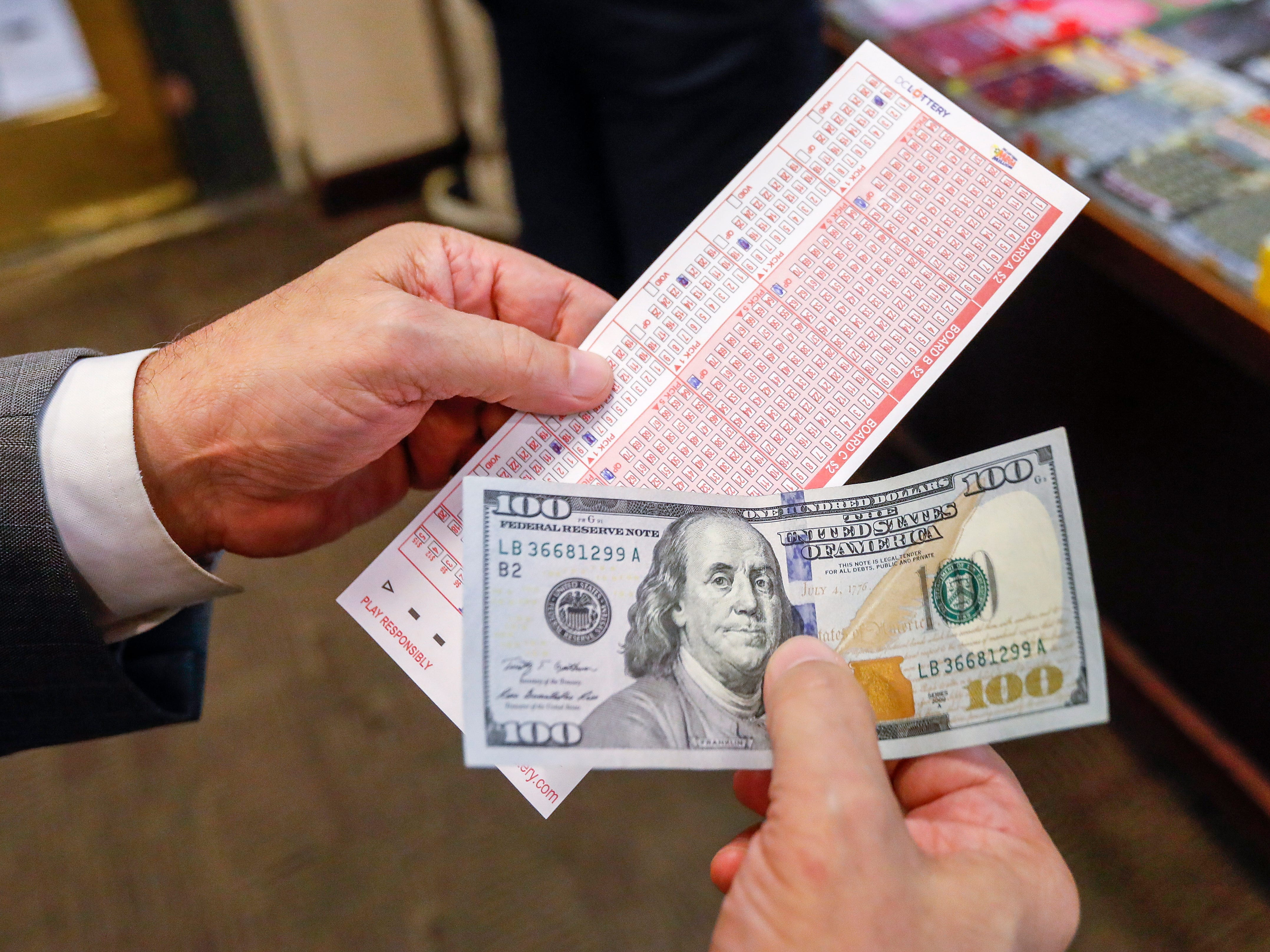 A buyer prepares to purchase Mega Millions lottery tickets at a retailer in Washington, D.C.,  Oct. 22, 2018.
