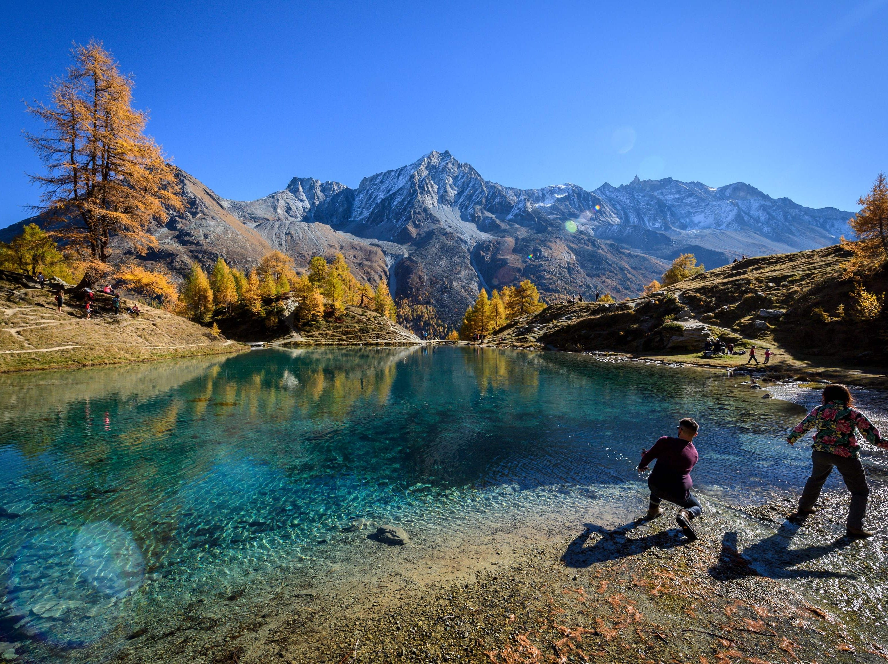 "Tourists throw stones in the ""Blue Lake"" surrounded by larch trees is seen on a warm autumn day on Oct. 20, 2018 above Arolla, western Switzerland."