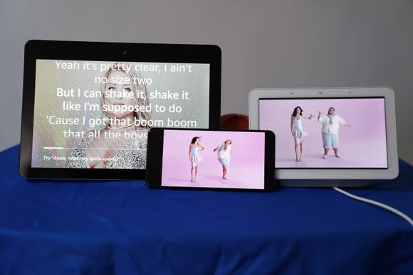 Watching a music video on Amazon Echo Show, Google Pixel 3 and Google Home Hub. The video plays on the Google devices, while the lyrics play over an image on Echo Show