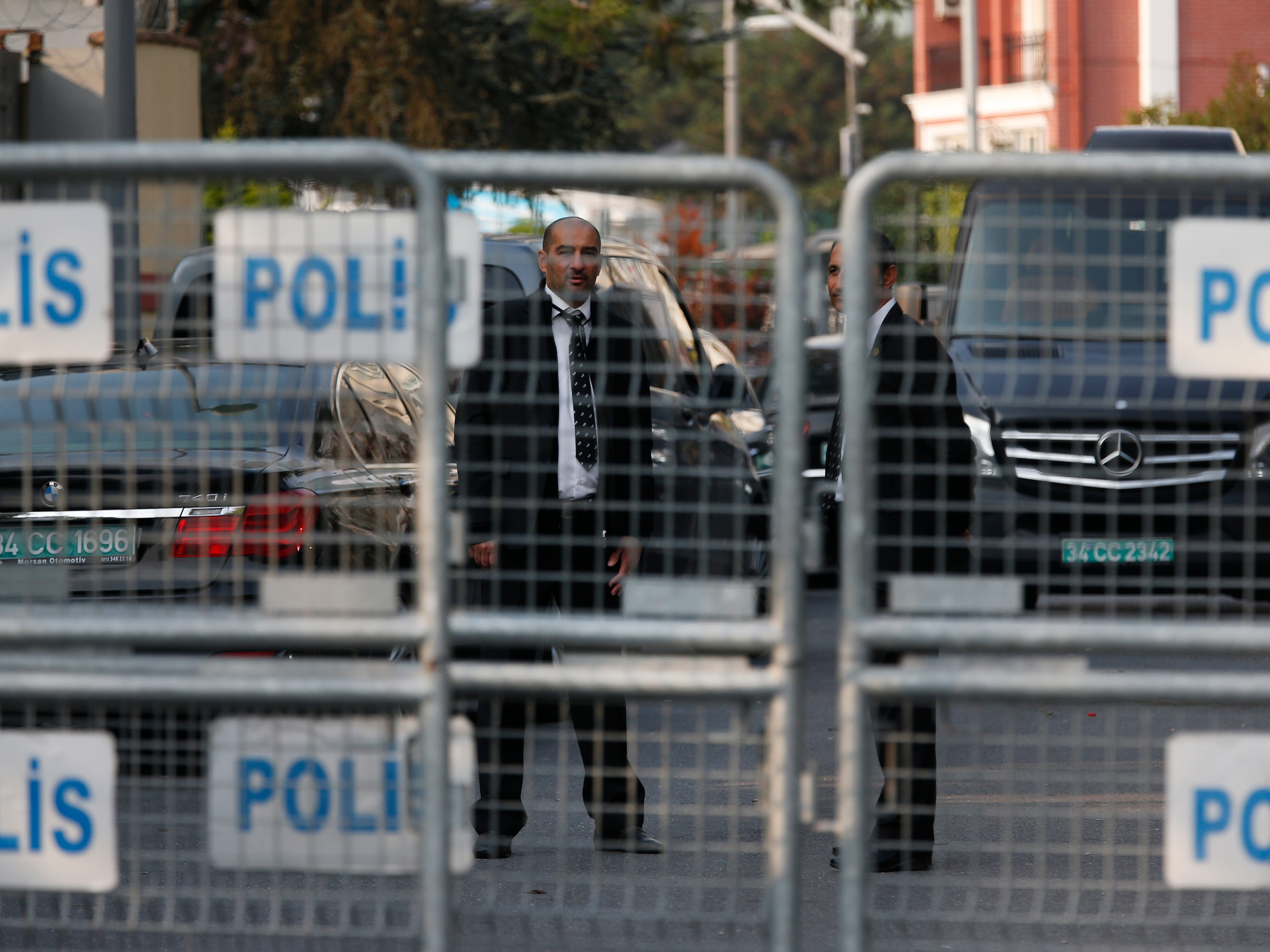 Security personnel guarding Saudi Arabia's consulate are seen behind barriers blocking the road leading to the diplomatic mission, in Istanbul, Monday, Oct. 22, 2018.