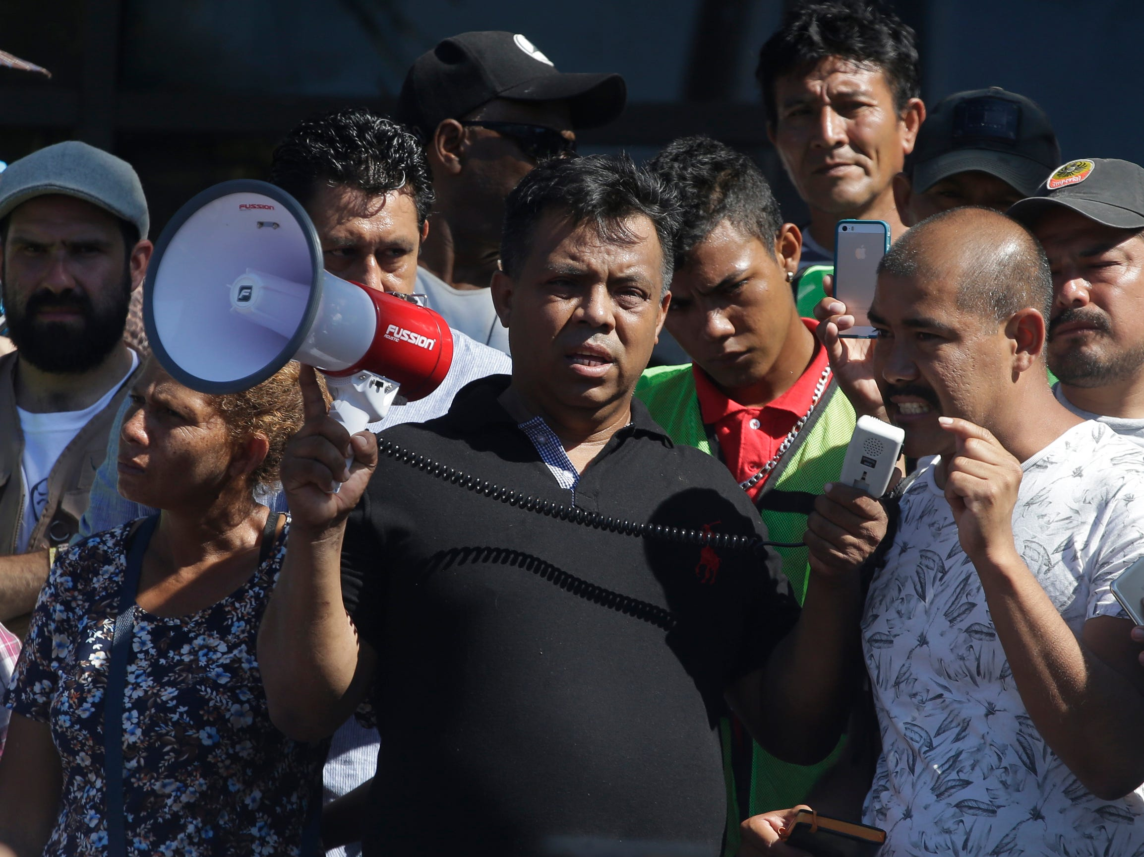"Migrant activist Irineo Mujica, center, holds a megaphone as a Central American migrant speak to reporters during a press conference in Tapachula, Mexico, Monday, Oct. 22, 2018. ""It is a shame that a president so powerful uses this caravan for political ends,"" said Mujica of the group Pueblo Sin Fronteras or People Without Borders, which works to provide humanitarian aid to migrants."