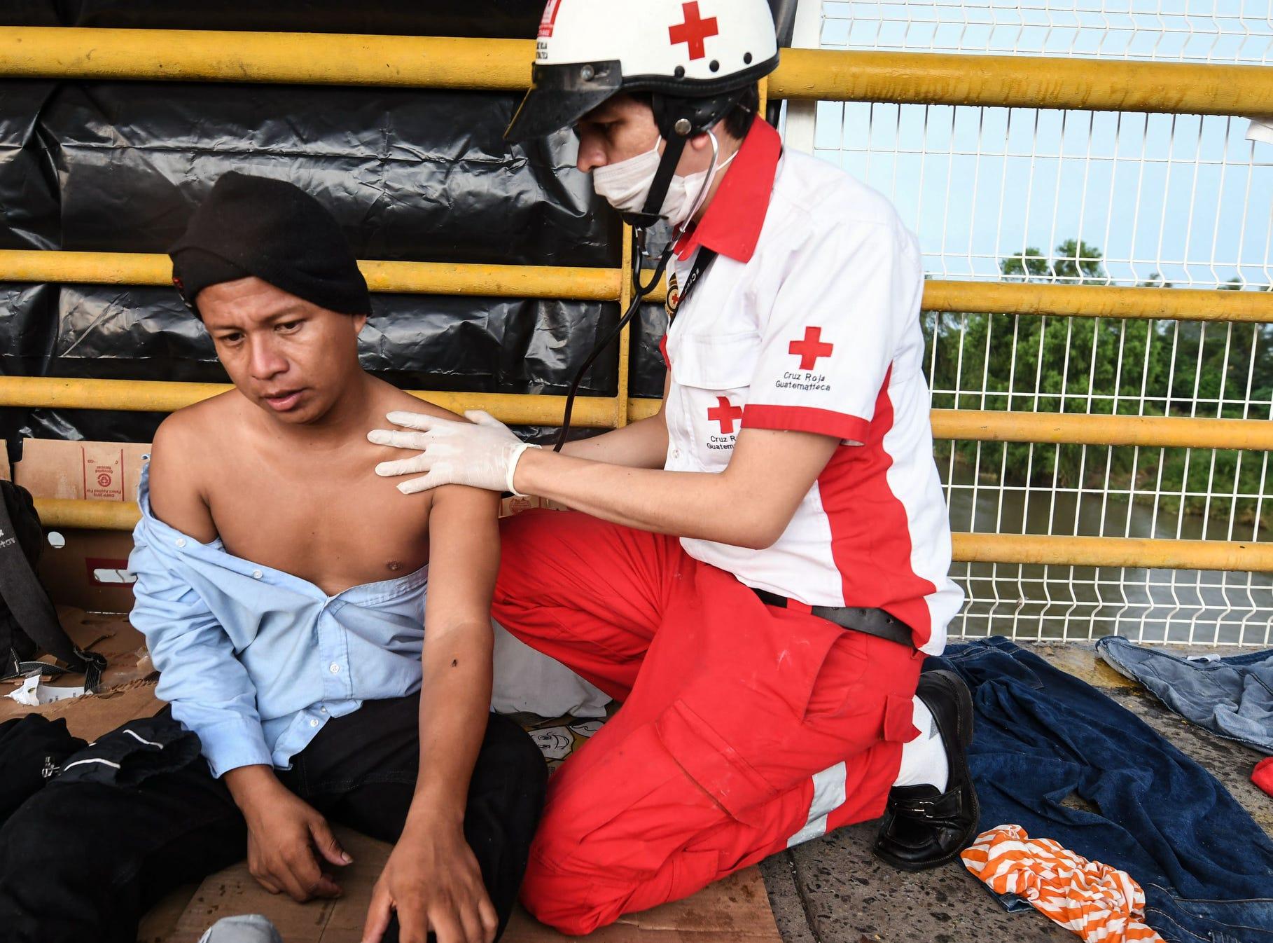 A member of the Guatemalan Red Cross attends an Honduran migrant heading in a caravan to de US, in Ciudad Tecun Uman, Guatemala.
