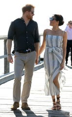 Prince Harry and Duchess Meghan hold hands while taking a walk along Kingfisher Bay Jetty during a visit to Fraser Island, Australia, on Oct. 22, 2018.