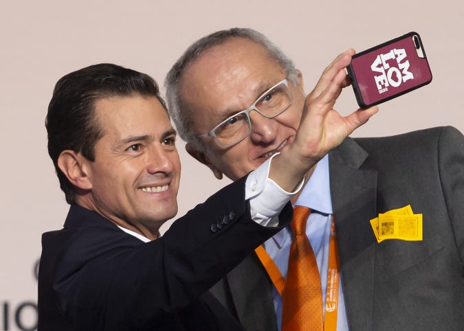 Mexican President Enrique Pena Nieto takes a selfie with the next negotiator of the North American Free Trade Agreement (NAFTA) Jesus Seade Kuri (R) during the 17th Mexico Business Summit 'Facing the strategic challenges of Mexico and the Region', at the Guadalajara Expo, in Jalisco, Mexico, Monday. Pena Nieto warned that the Central American migrants of the caravan heading to the United States who do not respect the law will be unable to reach the country or remain in Mexico.