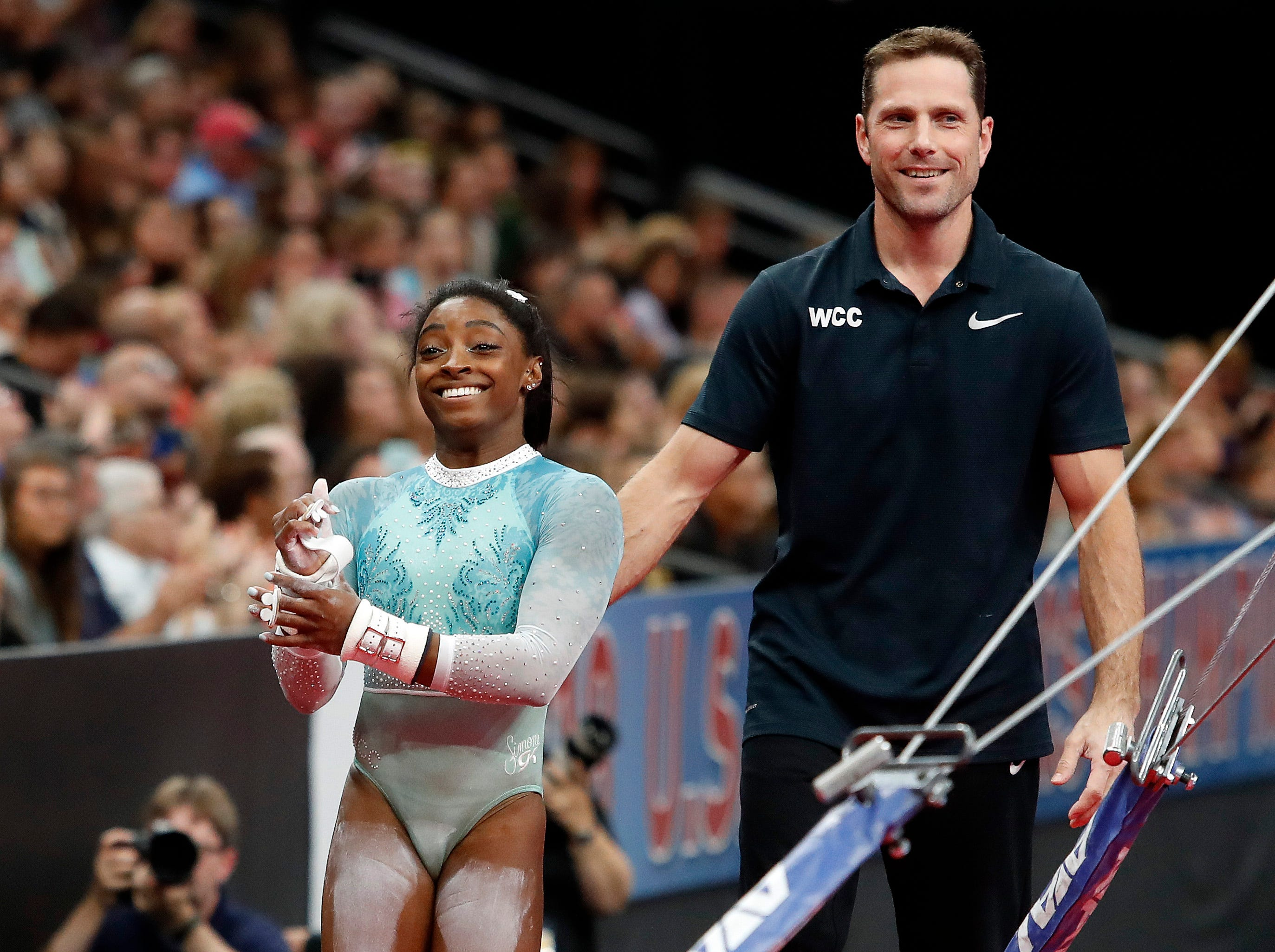 With coach Laurent Landi, Simone Biles smiles after competing on the uneven bars during the U.S. Gymnastics Championships at TD Garden on Aug. 19, 2018.