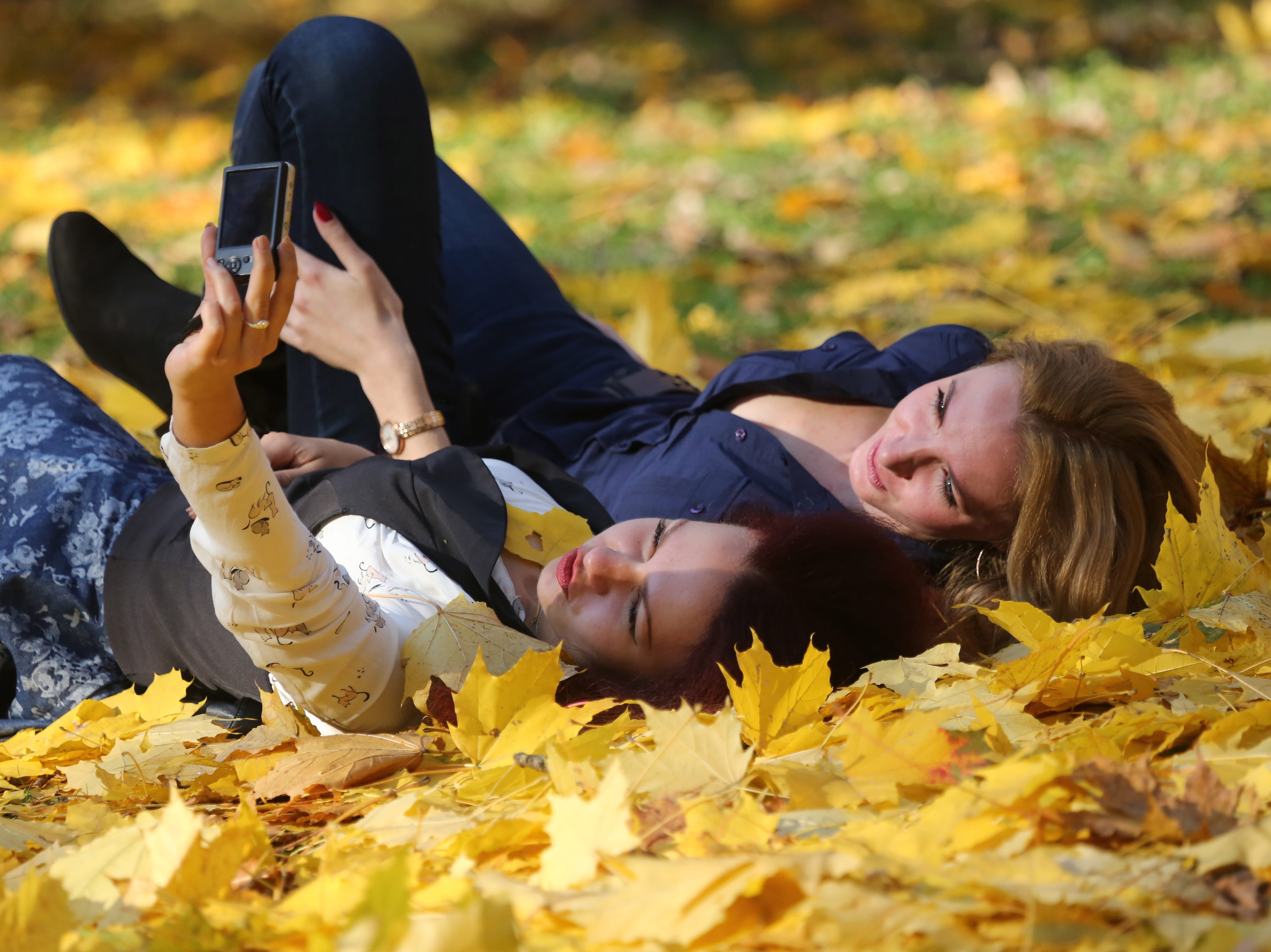 Young women take pictures on seasonal leaves in a central park on a sunny day in Minsk, Belarus on Oct. 18, 2017.