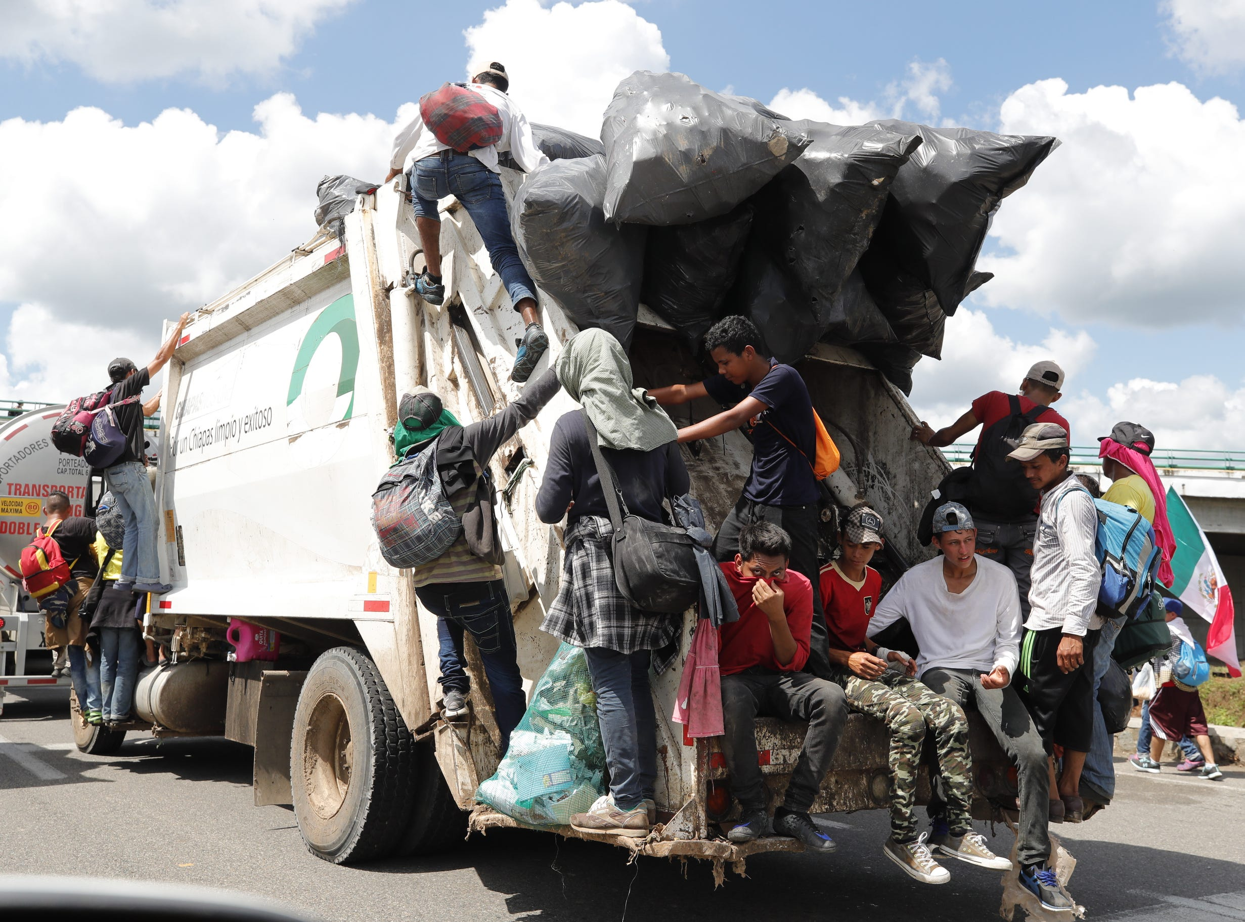Migrants hitch rides on all sorts of on vehicles, as they continue on another stretch of Mexican territory towards the United States, in this case a garbage truck.
