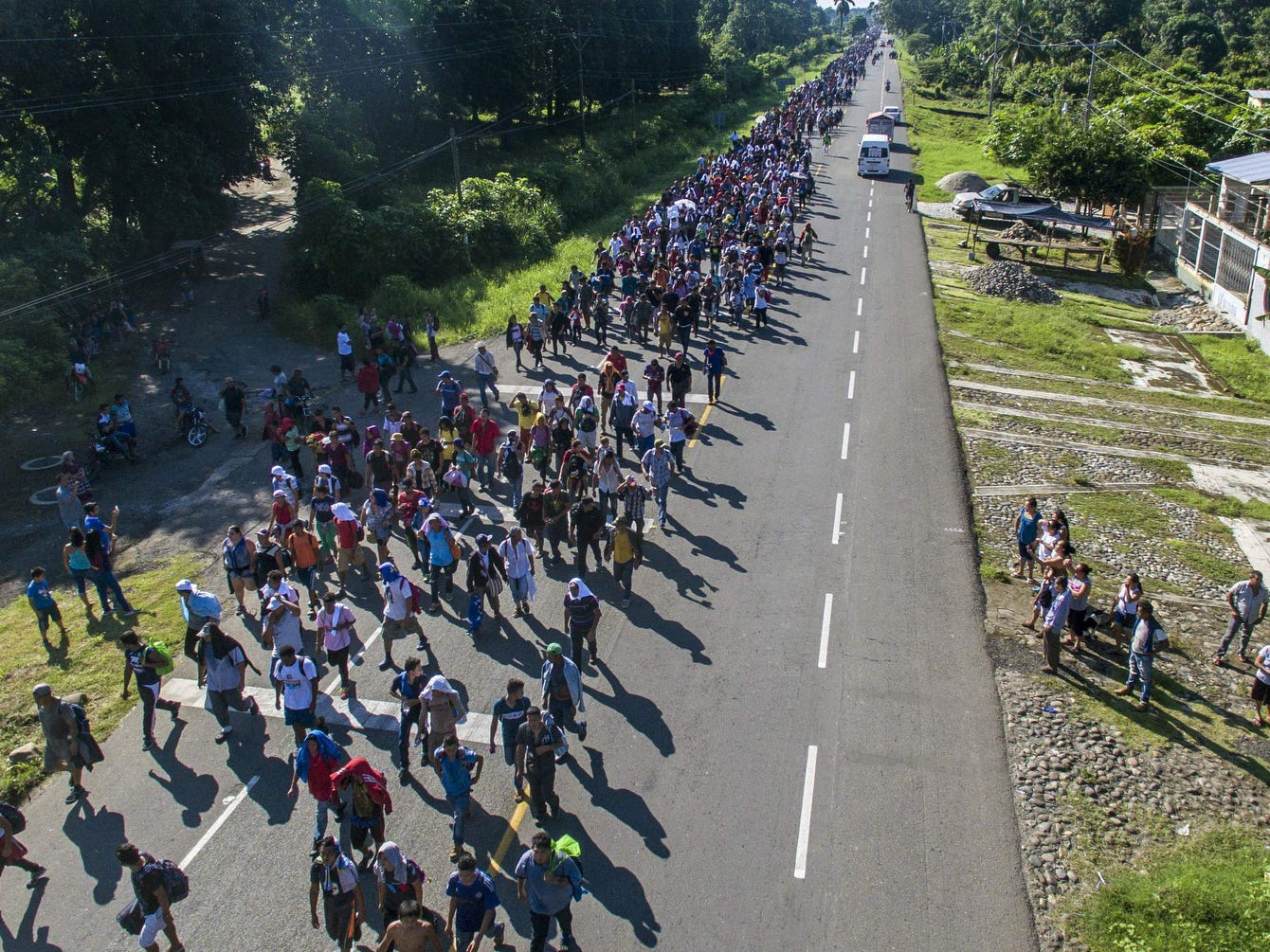 "An aerial view of Honduran migrants heading in a caravan to the US, Sunday, on the road linking Ciudad Hidalgo and Tapachula, Chiapas state, Mexico. President Trump called the caravan's approach a national emergency and said he has alerted the US border patrol and military, setting the stage for a confrontation when the swelling mass of migrants reach the border.""We will now begin cutting off, or substantially reducing, the massive foreign aid"" that the United States provides to Guatemala, Honduras and El Salvador, he said."