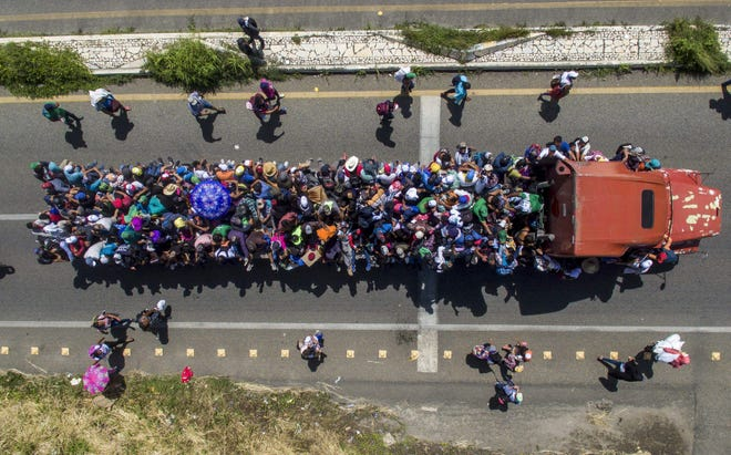 Miigrants hitch a ride on a truck as they take part in a caravan heading to the US, in the outskirts of Tapachula, on their way to Huixtla, Chiapas state, Mexico.