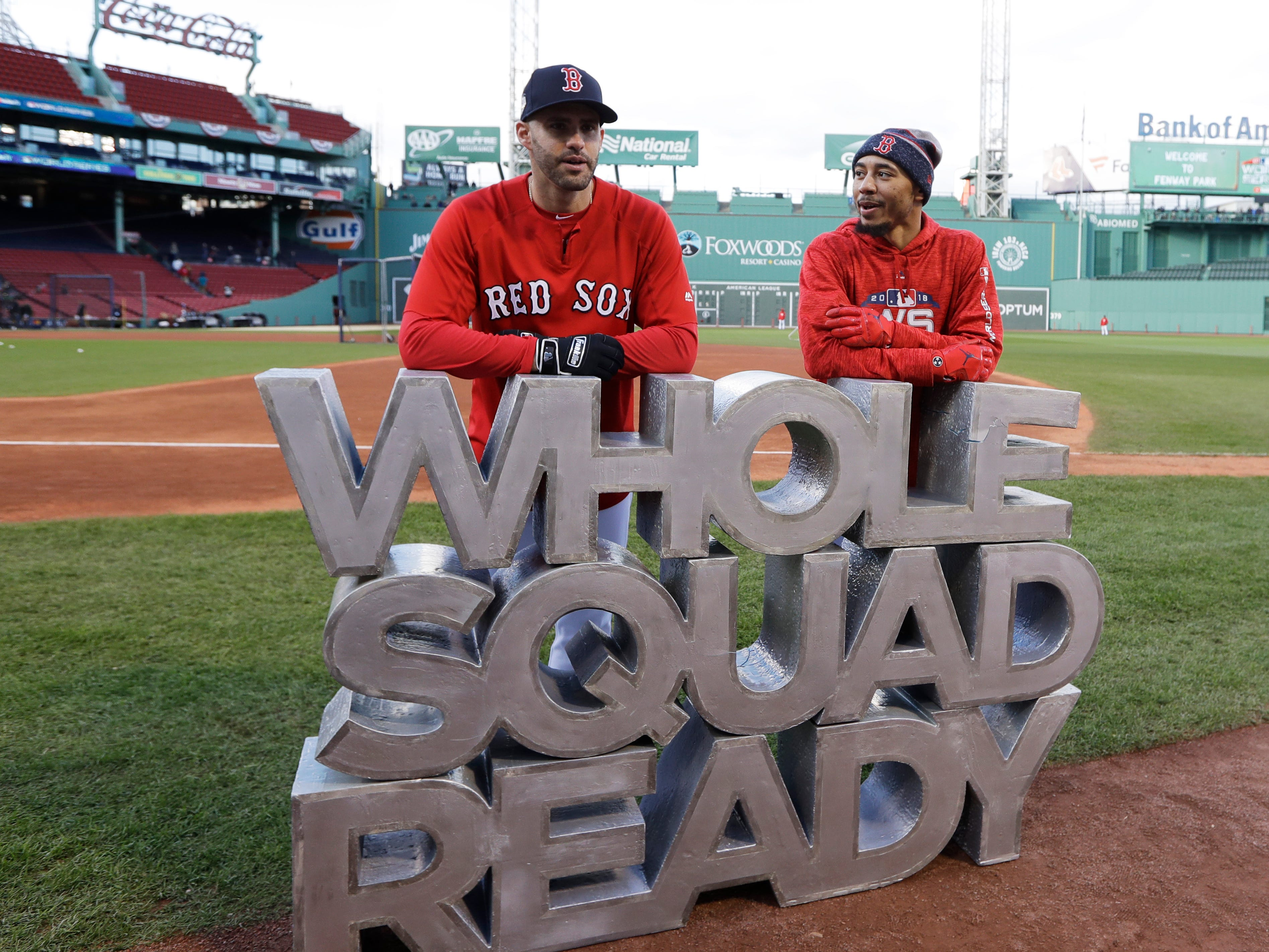 Red Sox's J.D. Martinez, left, speaks Mookie Betts stand behind their motto.