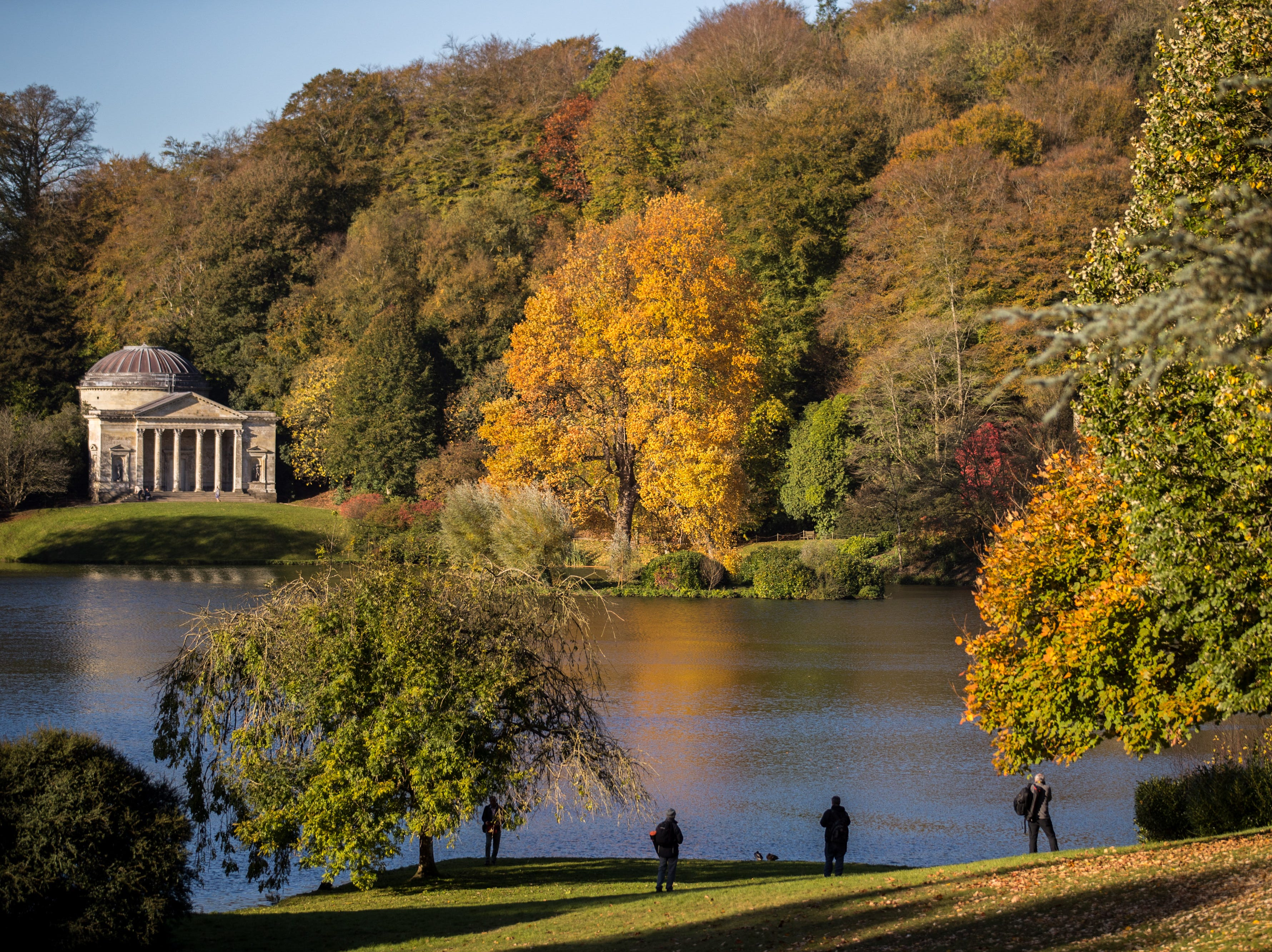 The sun shines on trees that are displaying their autumn colors surrounding the Palladian bridge and the lakeside Pantheon at the National Trust's Stourhead on Oct. 22, 2018 in Wiltshire, England.  Forecasters are warning that sub-zero temperatures and arctic winds will reach some parts of the UK by the end of this week, bringing to an end a stretch of mild autumn weather, which saw some areas in the south-east enjoying temperatures hitting 68F on the weekend.