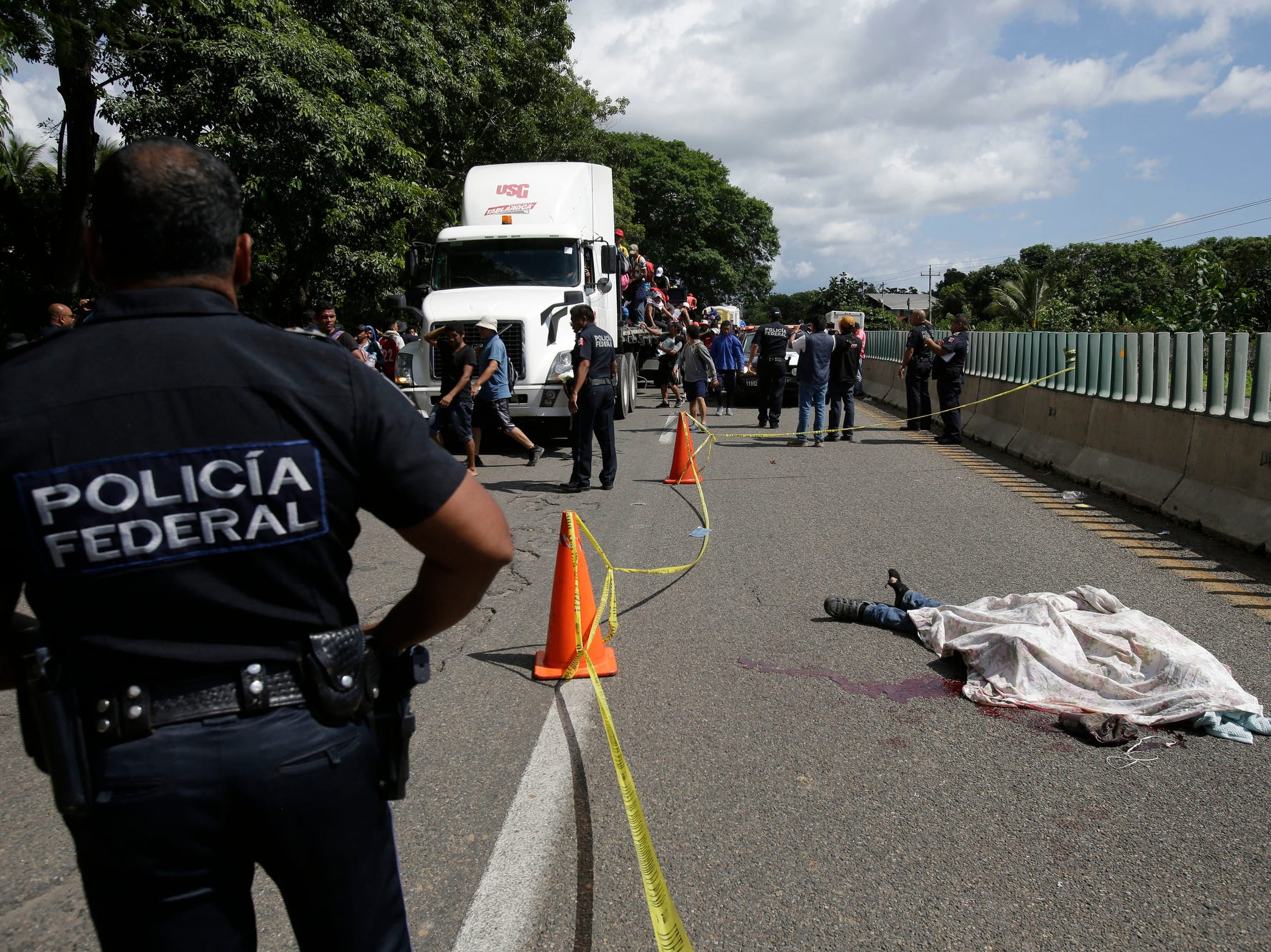 A Central American migrant, who fell from the back of a moving vehicle and died, lies on a highway covered by a sheet outside of Tapachula, Mexico, Monday. Motorists in pickups and other vehicles have been offering the Central American migrants rides, often in overloaded truck beds, as the group of about 7,000 people heads to the U.S. border.