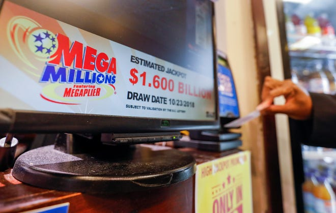A customer checks their previous draw tickets before purchasing Mega Millions lottery tickets at a retailer in Washington, D.C., Oct. 22, 2018.