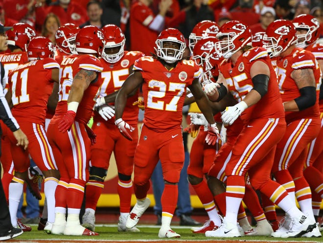 Chiefs running back Kareem Hunt (27) is congratulated by teammates after scoring a touchdown against the Bengals in the first half at Arrowhead Stadium.