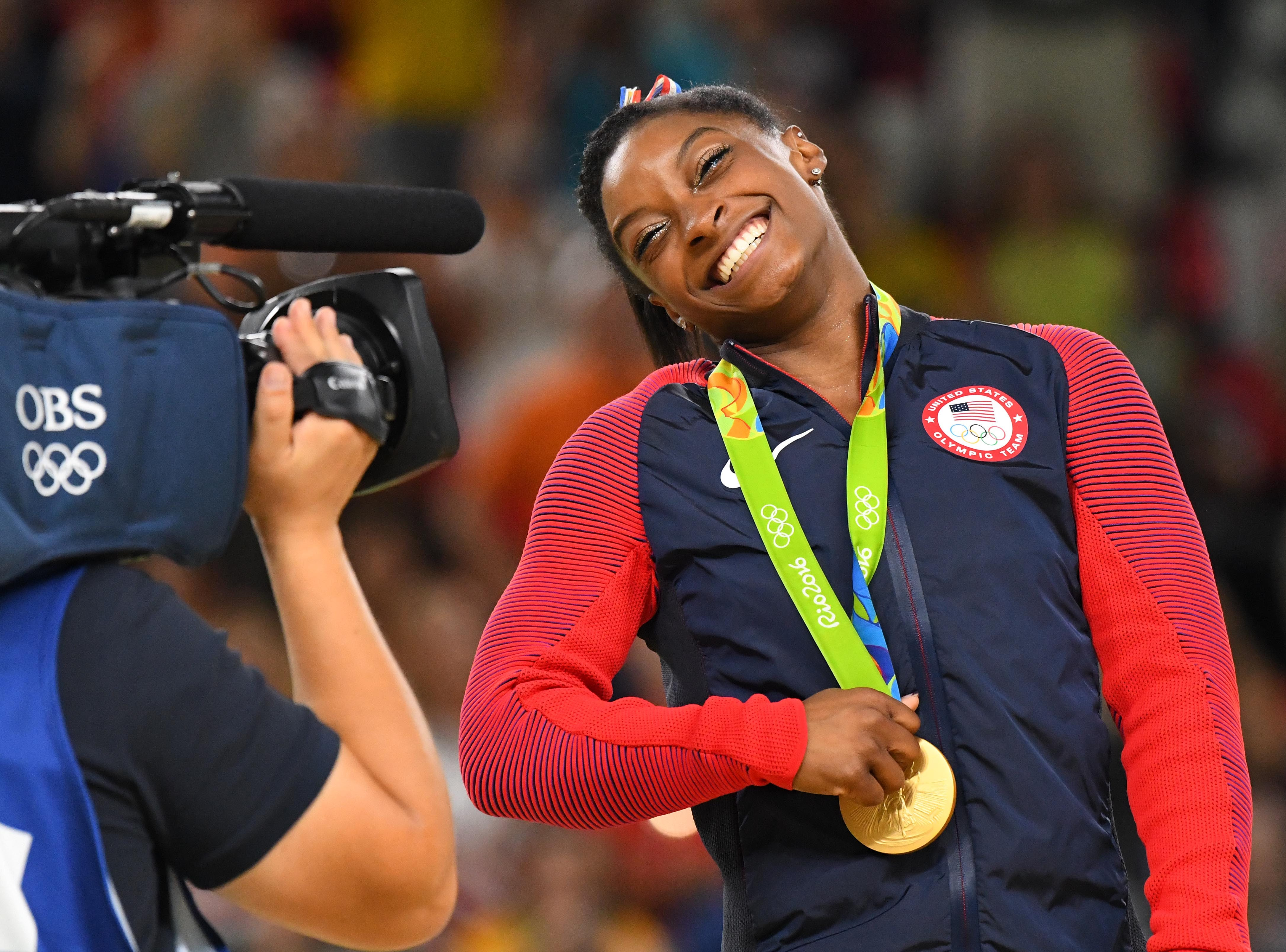 At the 2016 Olympics in Rio, Simone Biles celebrates after winning a gold medal in women's floor exercise.