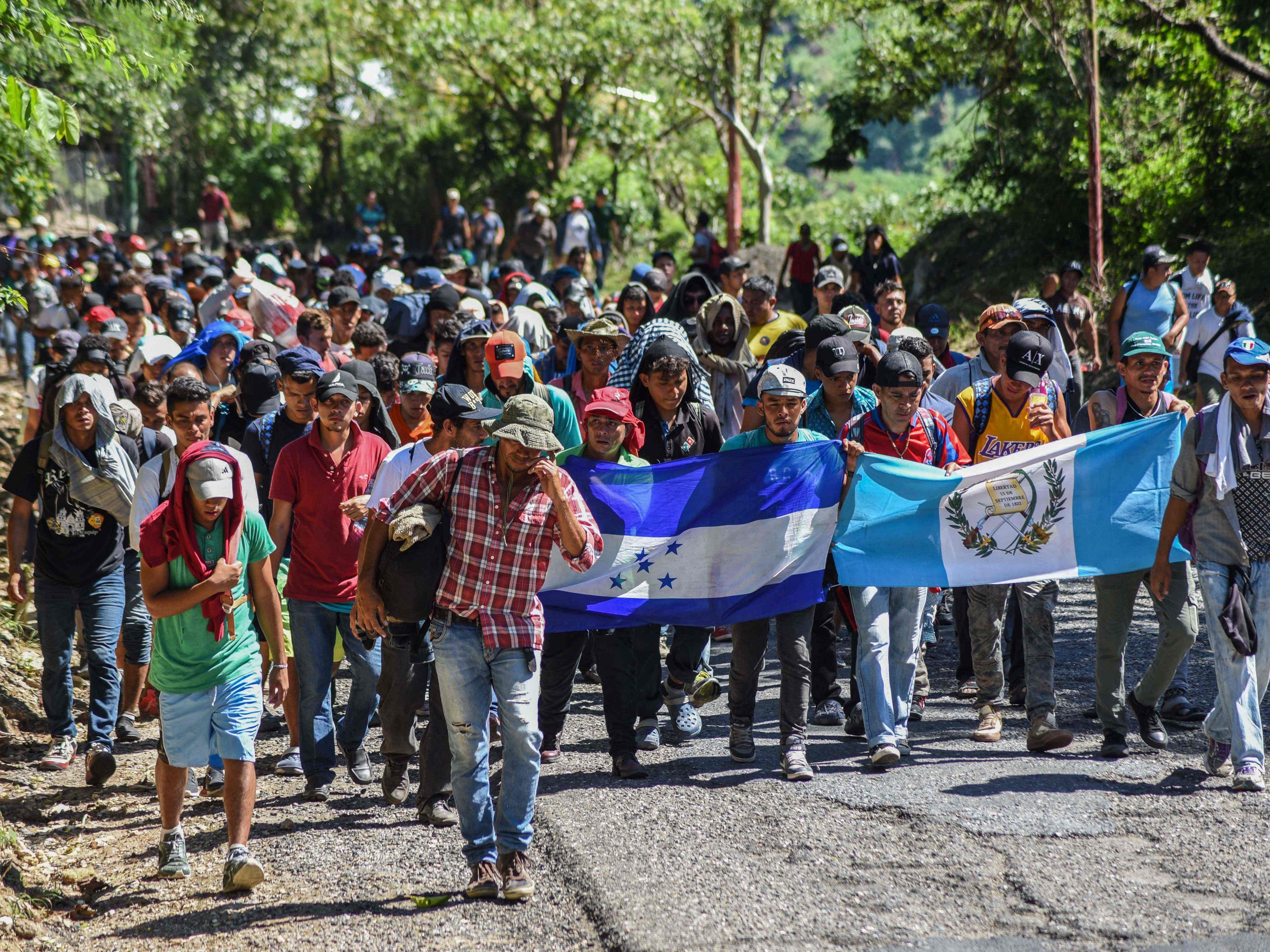 Migrants take part in a new caravan, Monday, heading to the US with Honduran and Guatemalan national flags in Quezaltepeque, Chiquimula, Guatemala.