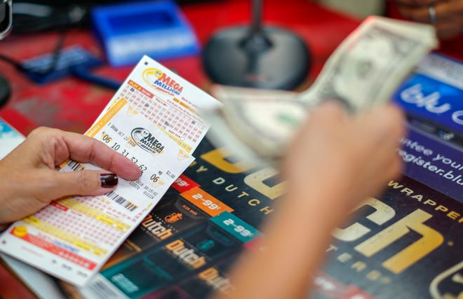 A customer purchases Mega Millions lottery tickets at a retailer in Arlington, Va., Oct. 22, 2018. The jackpot now stands at a record-breaking 1.6 billion dollars.