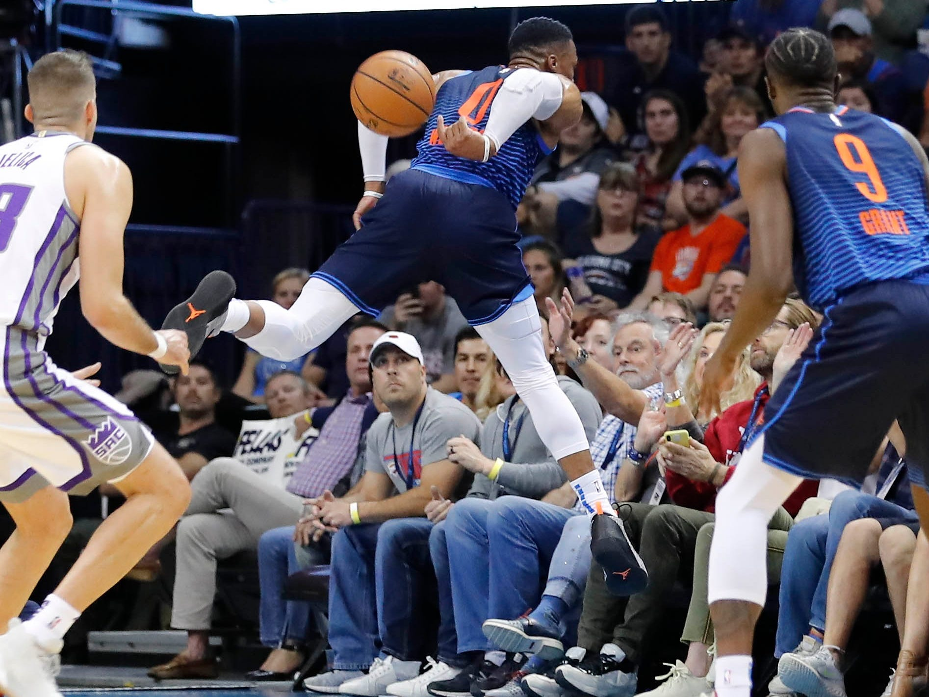 Oct. 21: Thunder guard Russell Westbrook (0) leaps into the first row of fans to save a loose ball from going out of bounds against the Kings in Oklahoma City.
