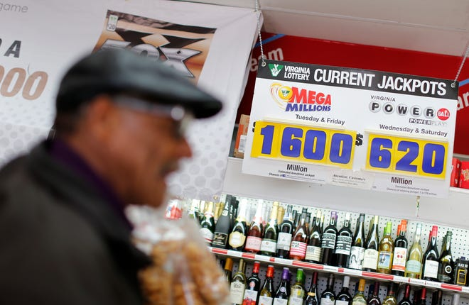 A sign shows the current Mega Millions and Powerball lottery jackpots as a customer purchases Mega Millions lottery tickets at a retailer in Arlington, Virginia Monday.