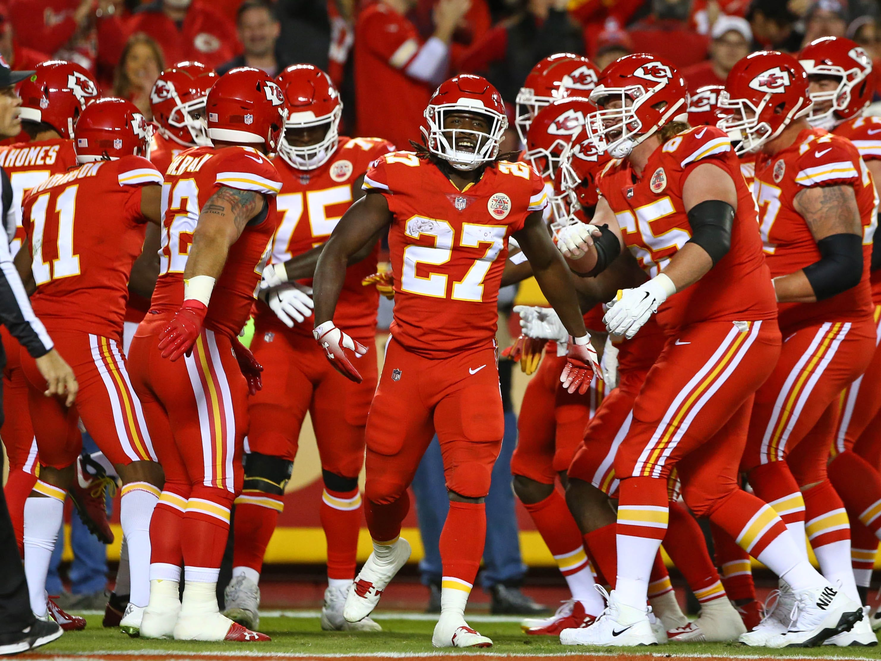 Kansas City Chiefs running back Kareem Hunt (27) is congratulated by teammates after scoring a touchdown against the Cincinnati Bengals in the first half at Arrowhead Stadium.