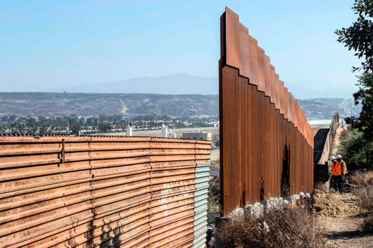 Construction workers are seen by a reinforced section of the U.S.-Mexico border fence in Tijuana, Baja Calif. state, Mexico.