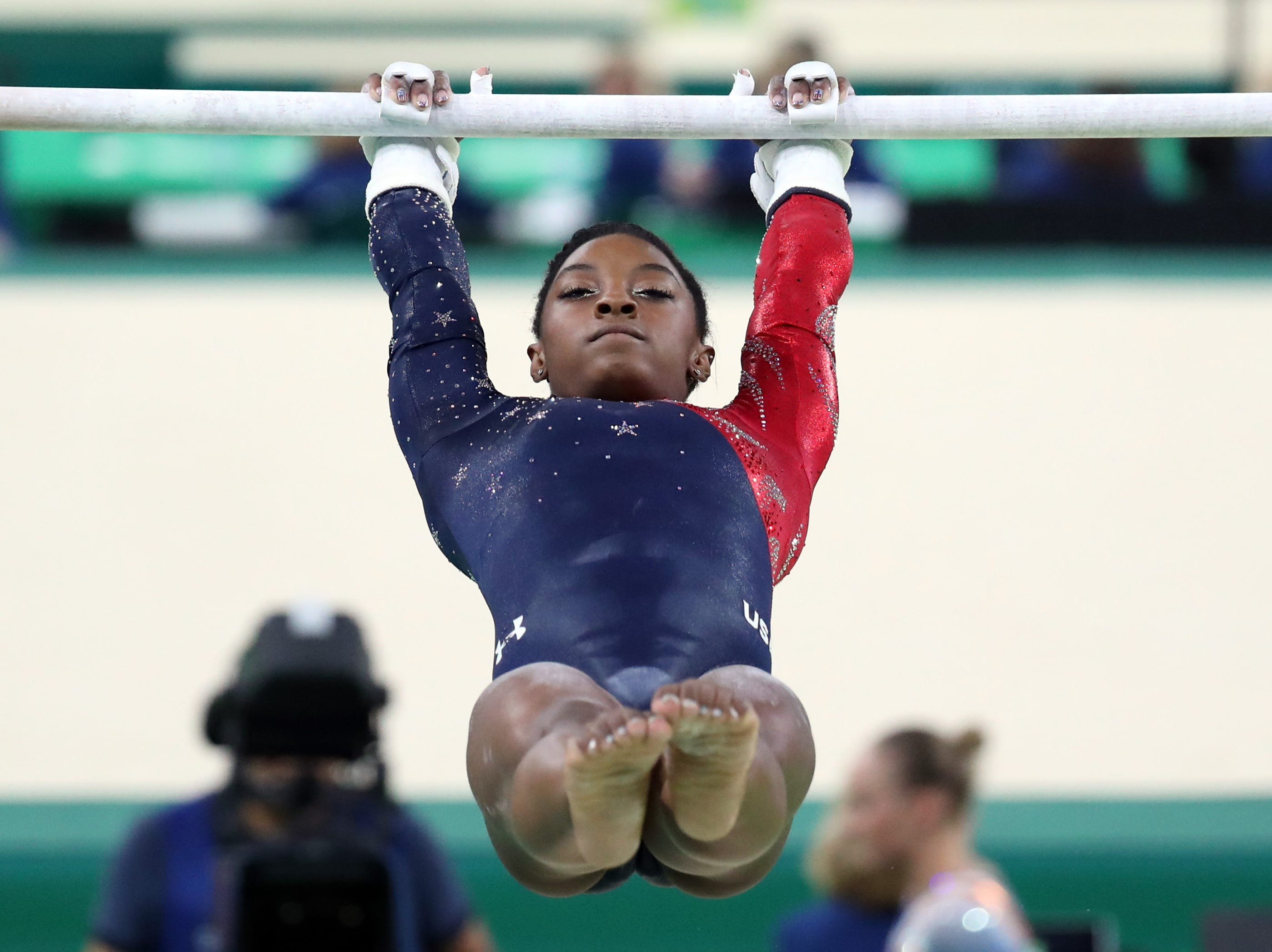 At the 2016 Olympics, Simone Biles competes on the uneven bars during  qualifying.