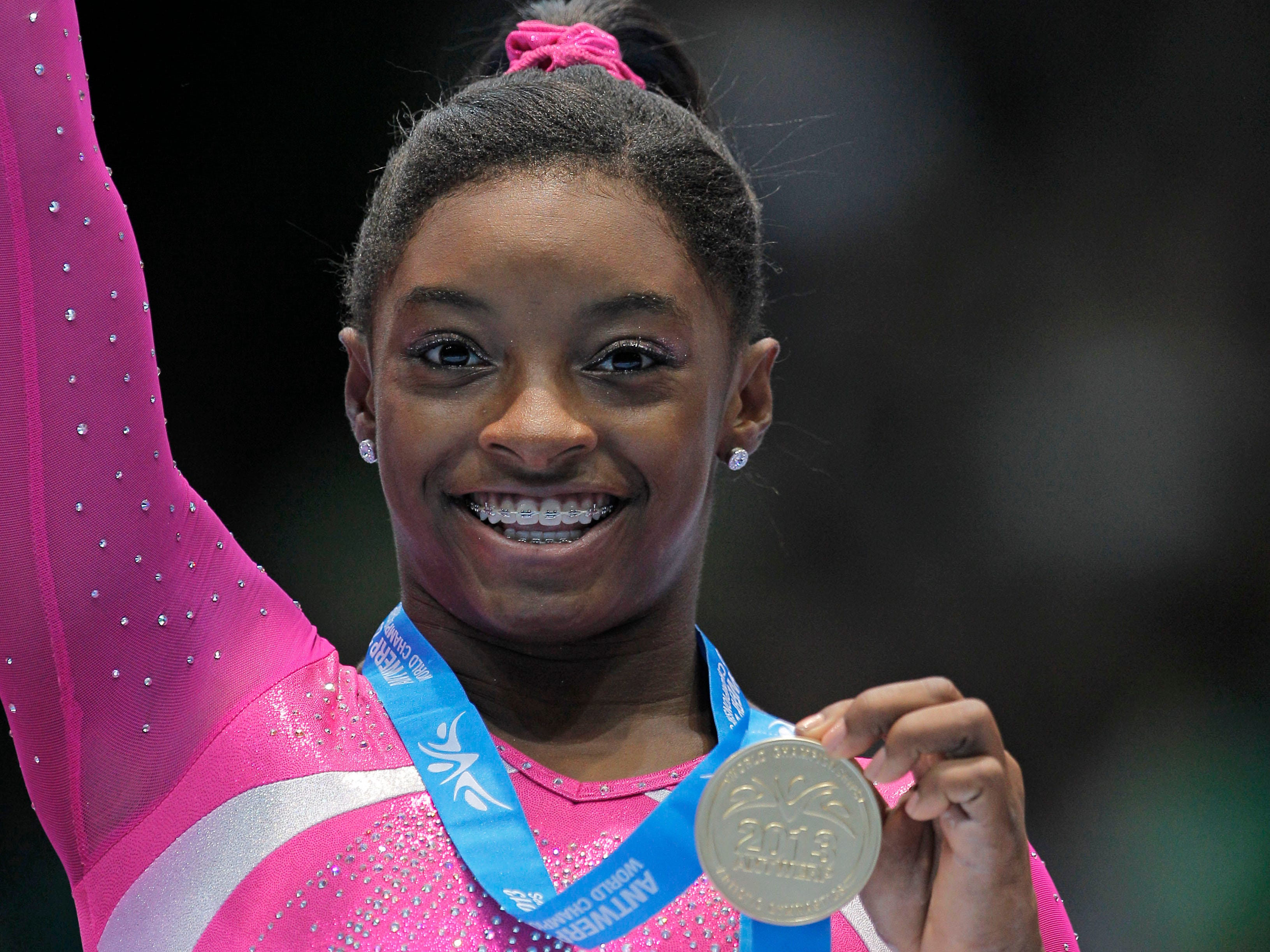 In 2013 at age 16, Simone Biles wins her first world championship gold medals in the all-around and floor exercise in Antwerp, Belgium.