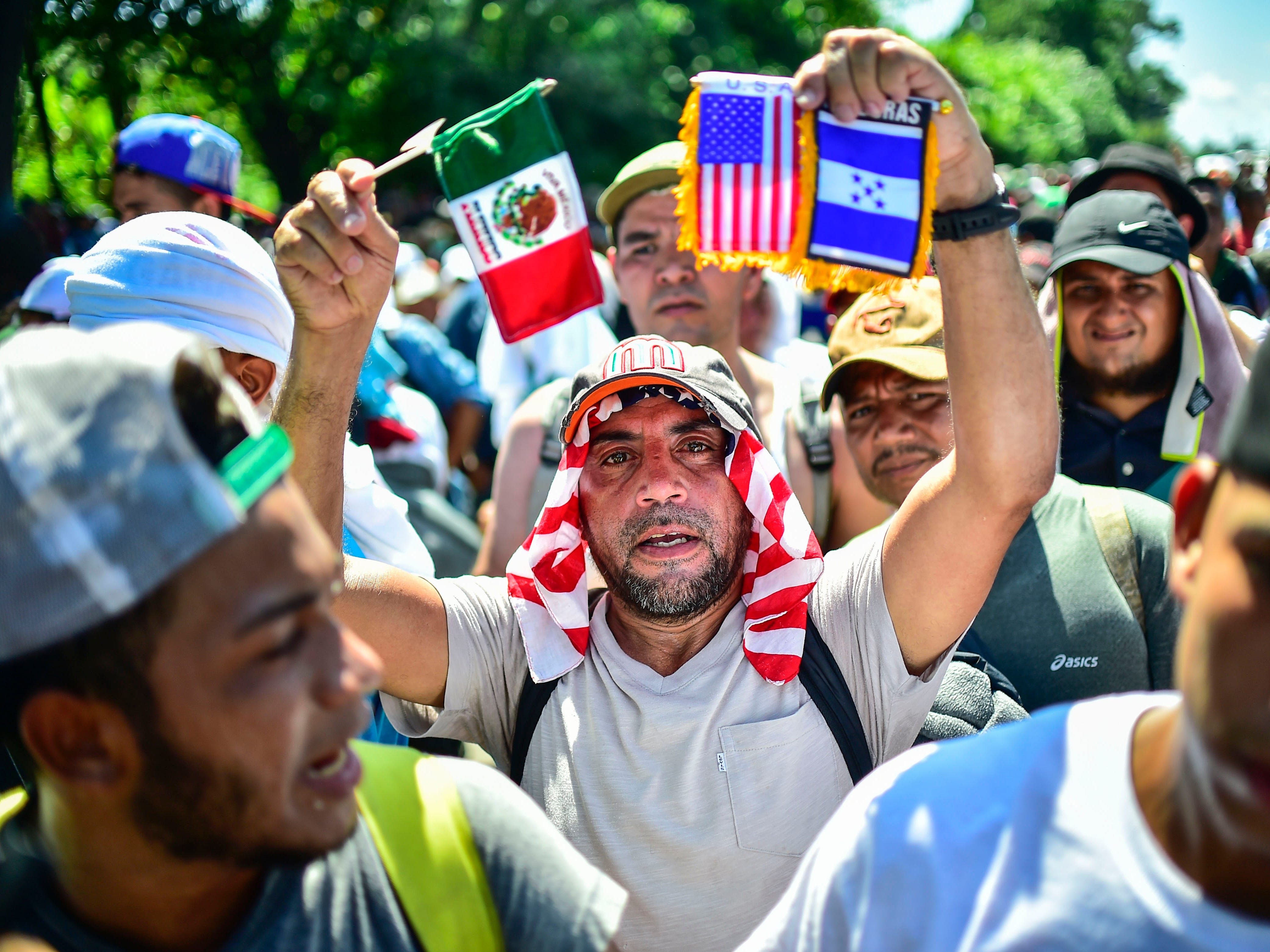 A migrant heading in a caravan to the US, holds Mexican, US and Honduran national flags on the road linking Ciudad Hidalgo and Tapachula, Chiapas state, Mexico, on October 21, 2018. - Thousands of Honduran migrants resumed their march toward the United States on Sunday from the southern Mexican city of Ciudad Hidalgo, AFP journalists at the scene said.