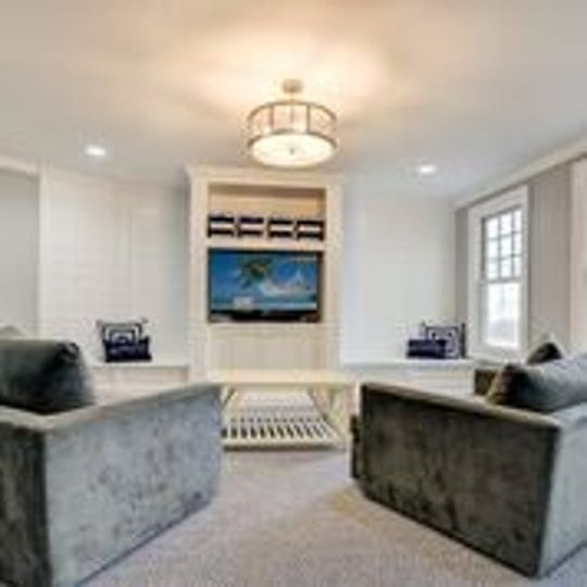 The media room features recessed lighting  and wall-to-wall carpeting.