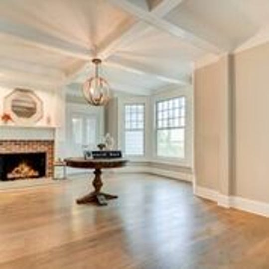 The foyer features coffered ceilings and custom windows.