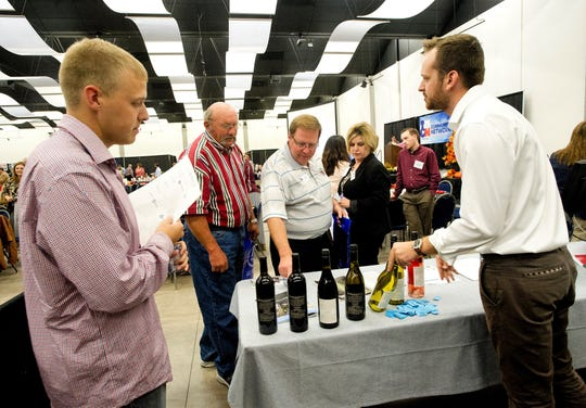 Matt Wolski, right, talks about wine bottle labels created by Found Media Group during an event at the 23rd Annual Texas Midwest Conference in 2016.