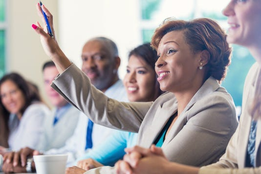 African American Businesswoman Raising Hand Asking Question In Business Conference