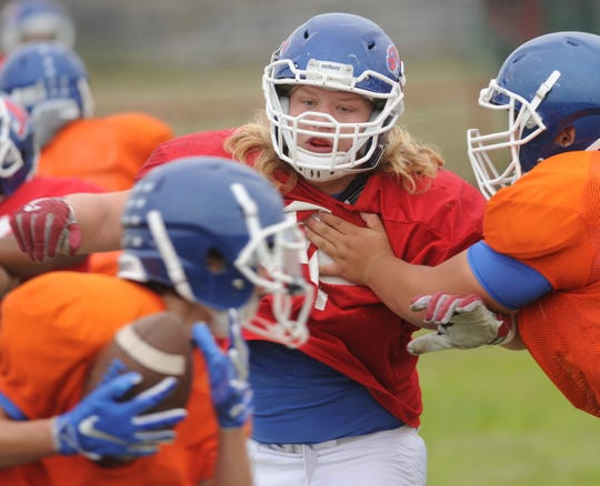 Cooper nose guard Colton Grimes, center, eyes the ball while a JV defender tries to block him during practice Monday at the Cooper High School. Grimes is the Cougars' starting nose guard this season, after playing a reserve role his first year with the varsity in 2017.