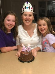 Katie Russell, of West Asheville, was diagnosed with breast cancer five years ago. Here she celebrates her birthday this year with her daughters Renna, left, and Sophie.