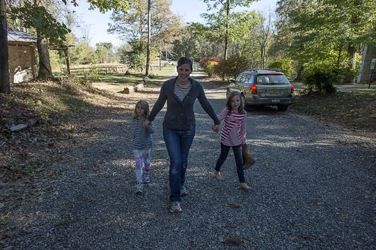 Katie Russell walks hand-in-hand with her two daughters Sophie, 5, left, and Renna, 8, left, on a road behind their house on the Asheville School campus Oct. 20, 2105. Russell was diagnosed with breast cancer in 2013.