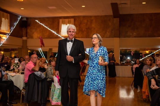 Breast cancer survivor Patricia Gray models in the Here's Hope Fashion Show and Luncheon fundraiser for the Hope Chest for women Oct. 20, escorted by friend Buncombe County Clerk of Court Steve Cogburn.