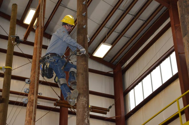 Journeyman lineworker Dan Kilgore demonstrates climbing one of the utility poles in the pole barn that Consumers Energy uses to train lineworkers on Oct. 16, 2018.