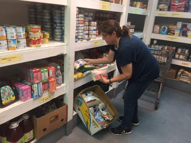 Paula Rebman, operations manager at Central Brevard Sharing Center, stocks shelves at the Cocoa nonprofit's food pantry. The Central Brevard Sharing Center is receiving a $28,000 Brevard County community-based organization grant for the current budget year.