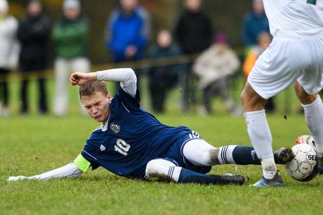Essex's Peter Osiecki (10) slides tackles a rice player during the boys soccer play down game between the Rice Green knights and the Essex Hornets at Essex High School on Tuesday afternoon October 23, 2018 in Essex.
