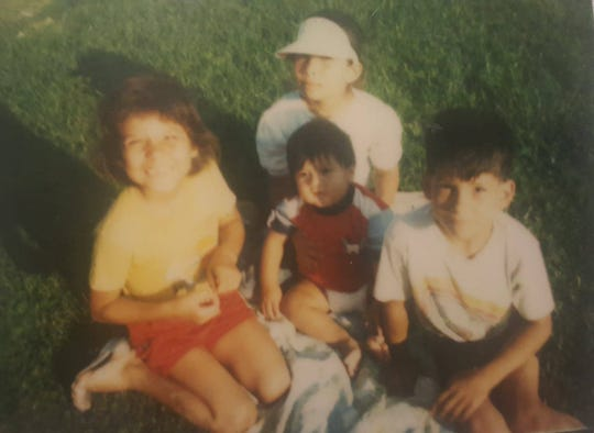 From left: Ruby Roberson Hall, Elisa Roberson (with the visor), infant Alex Quintana, and Tony Roberson. Ruby Roberson Hall said that she will soon hang this picture of her family up soon after spending most of her life having no pictures of her missing sister, Elisa, up at all.