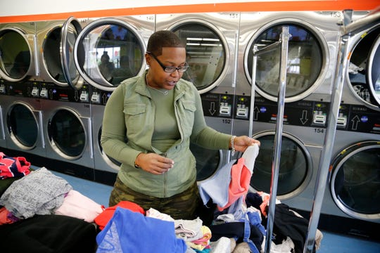 Mother of two, Lauren Phillips, 33, of Springdale, talks about her thoughts on the upcoming elections inside a laundromat in the Walnut Hills neighborhood of Cincinnati on Tuesday, Oct. 16, 2018.