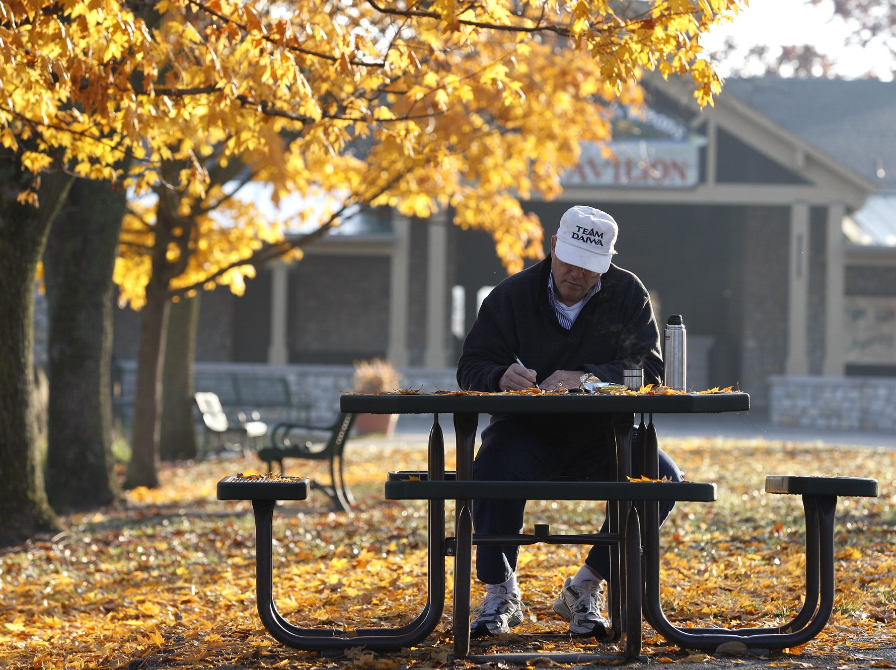 Frank Evans, of Springfield Township, works on a crossword puzzle as he enjoys a beautiful morning at Winton Woods Oct. 29, 2009.