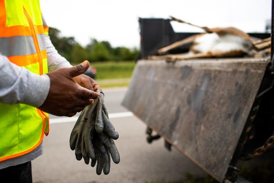 Robert Gardner carefully takes off his gloves after putting a deer into the back of the truck along Highway 374. As a TDOT operations technician, Gardner is tasked with removing roadkill and other hazards from Tennessee's roadways.