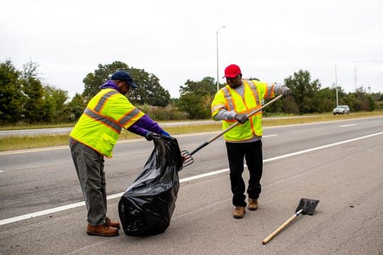 Frederick Lisenbee holds a trash bag as he and Robert Gardner pick up what they speculate is a cat carcass.