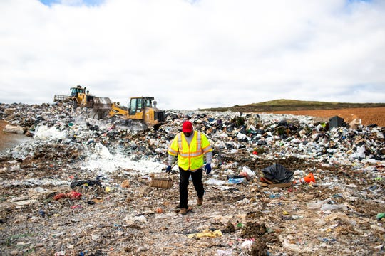 """TDOT worker Robert Gardner carries broom as he drops off roadkill and other road debris at Bi-County Solid Waste Management on Oct. 11 in Woodlawn. It's a dirty, smelly job, but, """"I'm from the farm; it doesn't bother me,"""" Gardner says."""